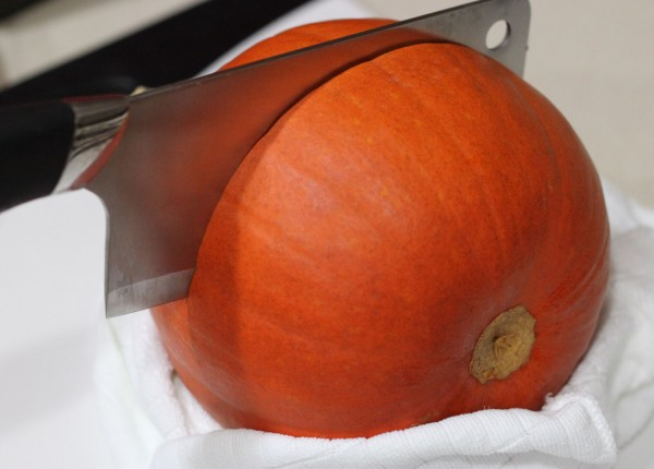 A pumpkin, wrapped at its base in a towel, with a meat cleaver halfway through.